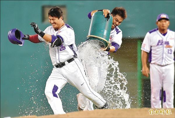 義大犀牛高國輝(左)9局下擊出再見安打,連兩天獲得單場MVP,隊友陳凱倫拿著冰桶倒向高國輝慶賀。(記者張忠義攝)