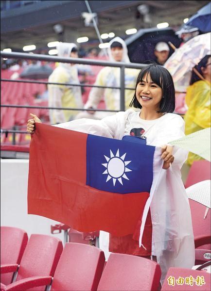 熱血球迷帶著國旗在雨中等候台灣隊出賽。(特派記者林正堃攝)