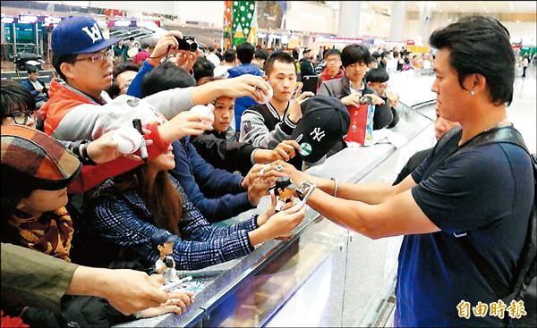 王建民(右)幫接機球迷簽名。(記者姚介修攝)