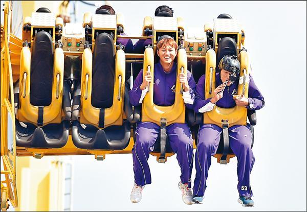 高國輝(左)和林哲瑄體驗「天旋地轉」遊樂設施。(記者張忠義攝)