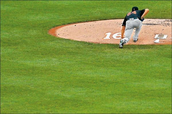 陳偉殷在主投本季第22場先發之前,蹲下來摸投手丘的畫 面,成為美國媒體捕捉到的動人鏡頭。 (法新社)