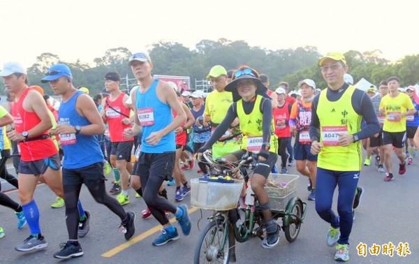 日月潭環湖馬拉松活動,因傷被截肢的「超馬媽媽」邱淑容(右2),以三輪腳踏車替代雙腳參賽情形。(記者謝介裕攝)
