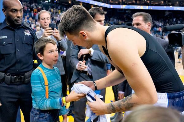 獨行俠小前鋒東契奇(右)贈送簽名球衣給被他壓到的小男孩。(今日美國)