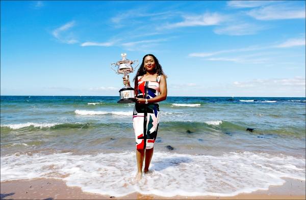 大坂直美澳網封后後,今將躍為WTA女單第一,昨在墨爾本海邊拿著獎盃合影。(路透)