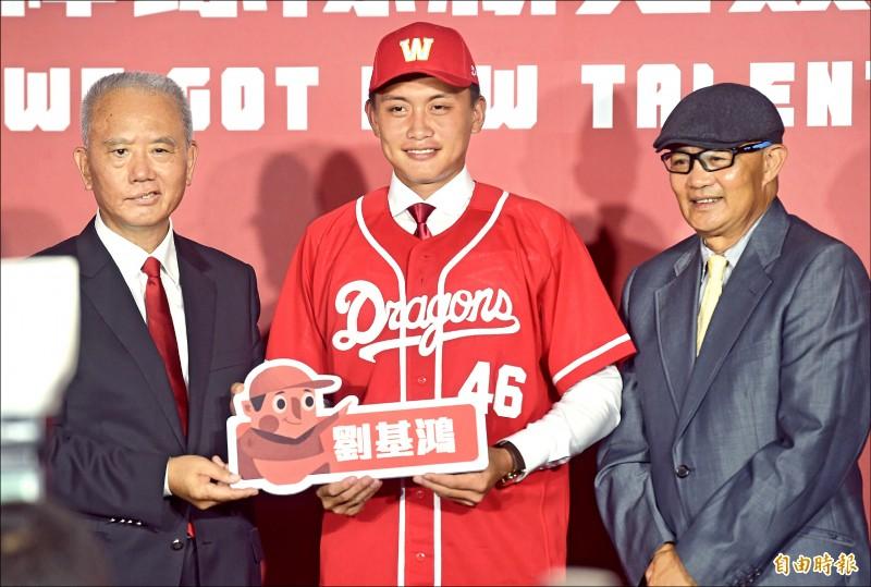 選秀狀元劉基鴻(中)以590萬簽約金正式加盟味全龍,陽介仁(右)為他穿上球衣。 (記者簡榮豐攝)