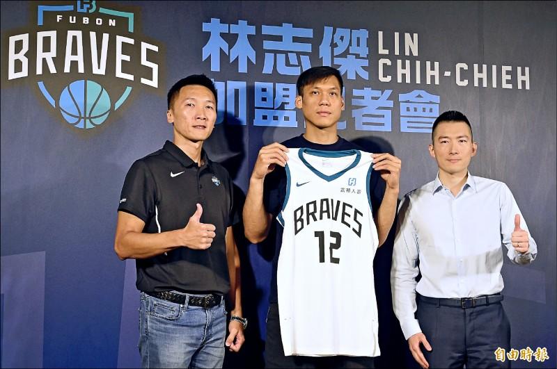 富邦勇士領隊蔡承儒(右)及總教練許晉哲(左)致贈12號球衣給林志傑。(記者叢昌瑾攝)