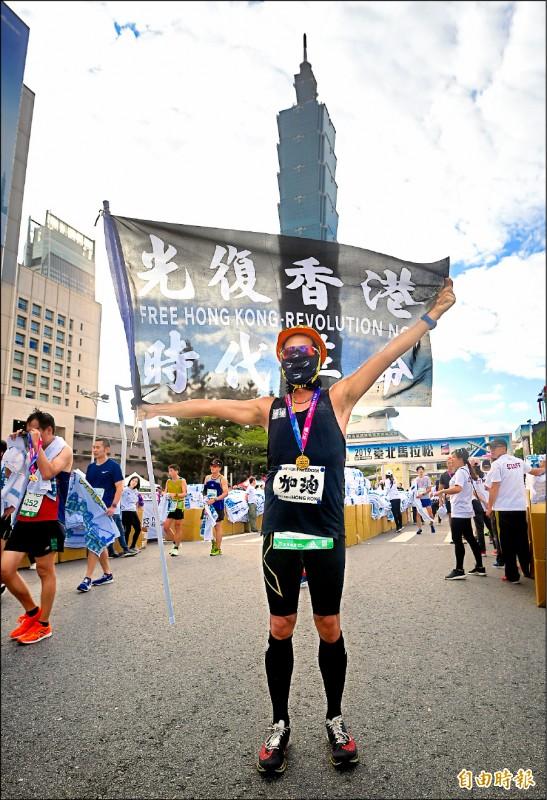 來自香港的跑者,身穿黑色跑衣,並舉著「光復香港,時代革命」的旗幟邁入終點,期盼藉由台北馬,向國際社會傳遞「護民主,挺自由」的訴求。(記者方賓照攝)