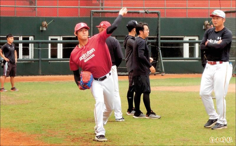 樂天桃猿投手王溢正(左)與隊友傳接球,總教練曾豪駒(右)在旁觀看。(記者徐正揚攝)